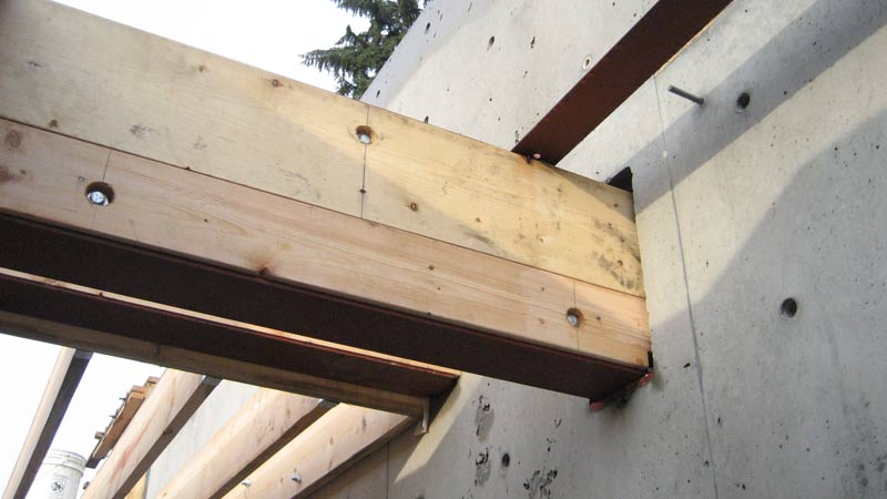 steel-beam-casing-attached-wth-bolts-steel-beams-attached-to-concrete-wall-wood-floor-joists-beyond