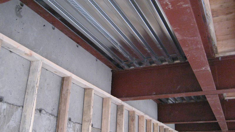 steel-beams-over-garage-attached-to-concrete-wall-with-qdeck-above-and-stud-wall-at-concrete-wall