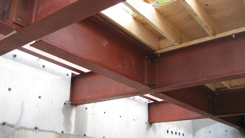 steel-floor-beams-over-garage-welded-connections-connected-to-concrete-wall-floor-joists-above