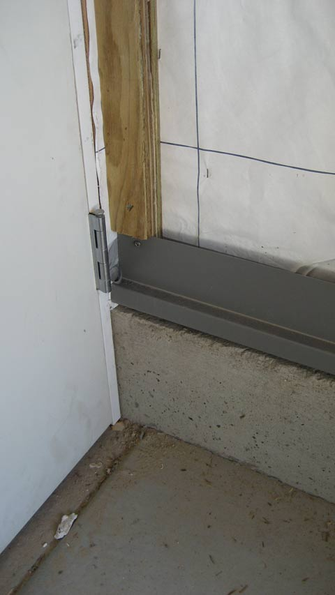 man-door-at-garage-door-and-flashing-over-concrete-wall