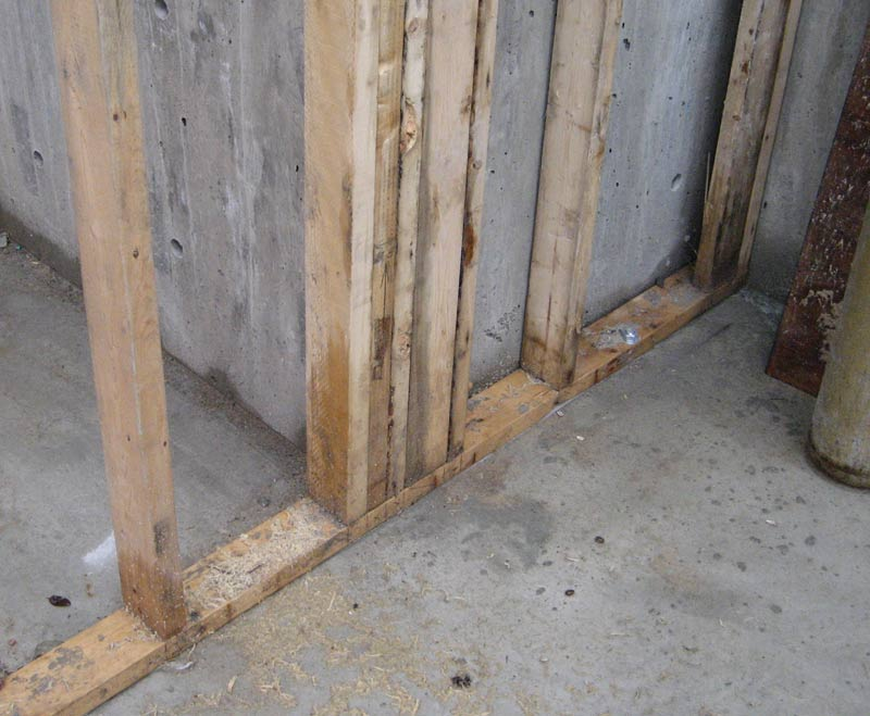 stud-wall-framed-at-concrete-wall-over-concrete-slab