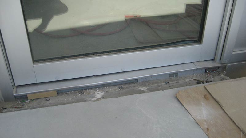 CUSTOM-STAINLESS-STEEL-DOOR-THRESHOLD-FLUSH-WITH-EXTERIOR-DECK----AT-PIVOT-GLAZED-DOOR