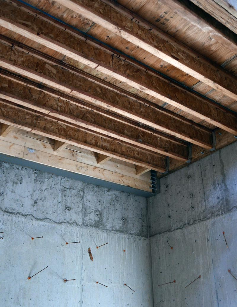 WOOD-JOIST-FLOOR-FRAMING-CONNECTED-ATTACHED-TO-CONCRETE-WALL