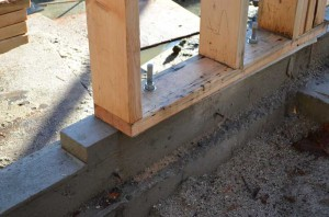 wood sill plate over foam gasket and concrete foundation wall wood