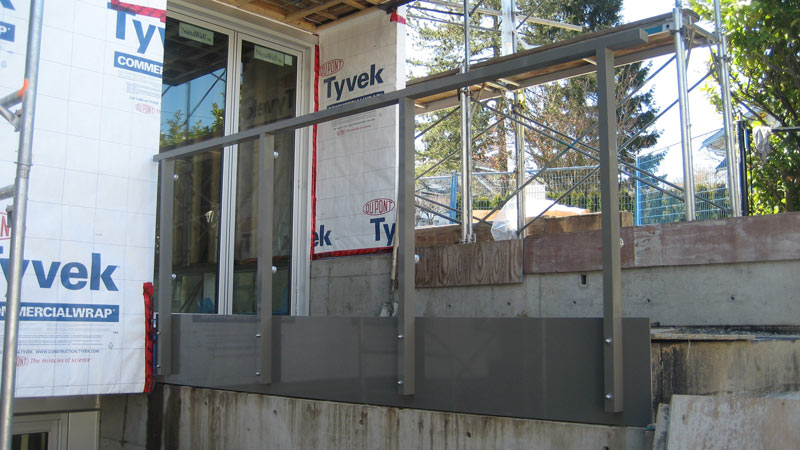 ALUMINUM-STANCHIONS-ATTACHED-TO-CONCRETE-WALL-THROUGH-A-PAINTED-METAL-FASCIA-PLATE-BEFORE-GLASS-GUARD-INSTALLATION