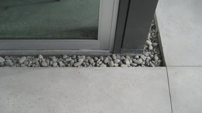 Trench-drain-between-sliding-door-and-concrete-slab-0-filled-with-river-rock-2
