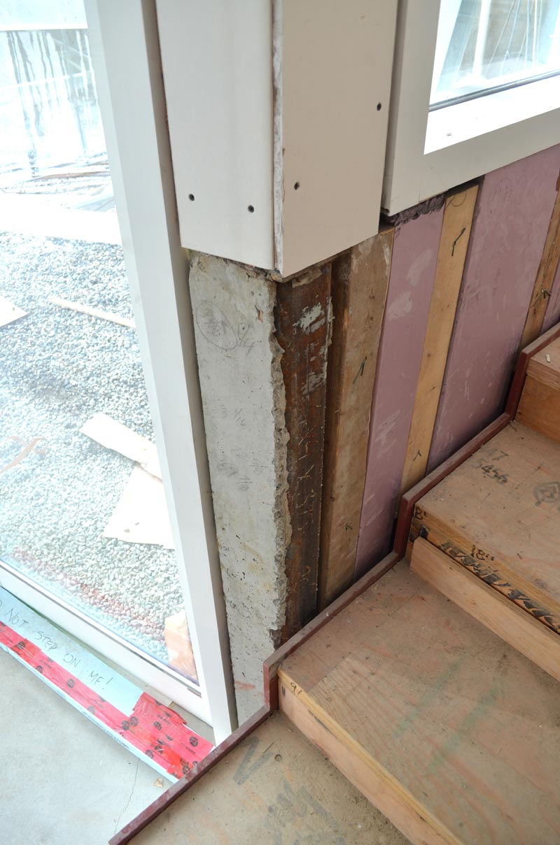 custom-profile-steel-stringer-stair-at-a-window,-parallel-to-a-concrete-wall-insulated-with-rigid-foam-insulation